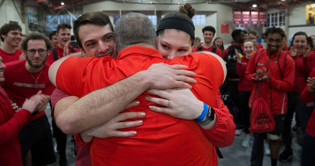 Track and field coach Roger Haynes embraces Payton Holmes and Aleeka Gentzler following their eng...