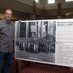 Associate Professor of Chemistry Brad Sturgeon poses with a poster that has a photo of the first ...