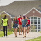 A group of students walk near Pattee Hall at Monmouth College. The college is continuing its comm...