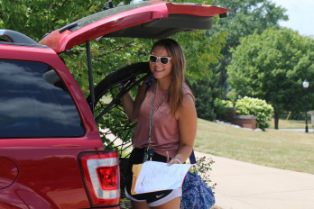 Student moving in at her car.